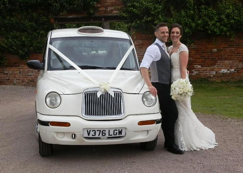 Bride and Groom leaning on London Taxi Wedding Car at Elvaston Castle
