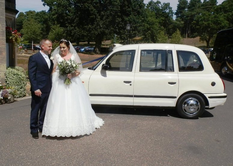 Bride and Groom beside London Taxi Wedding Car at Breadsall Priory