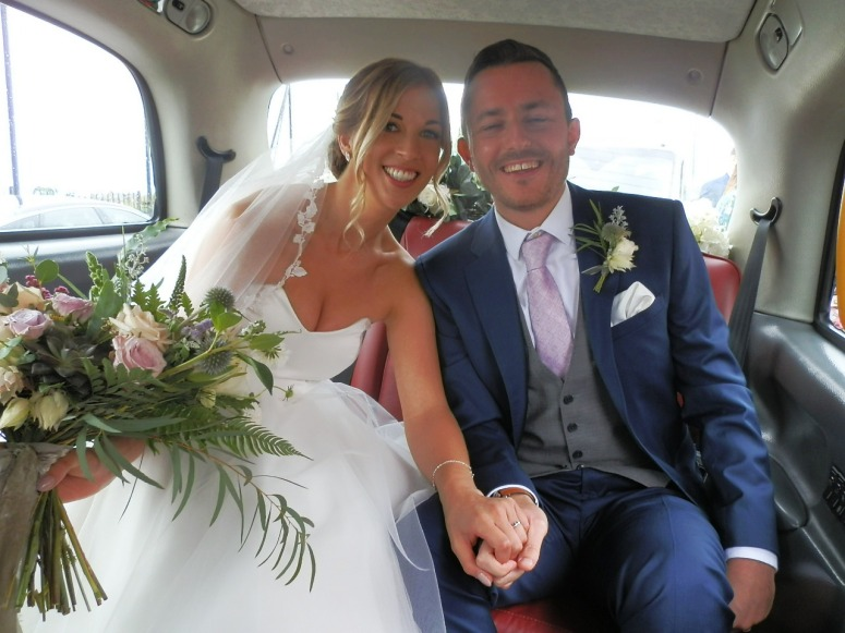 bride and Groom in rear of London Taxi Wedding Car at The Pumping House Ollerton