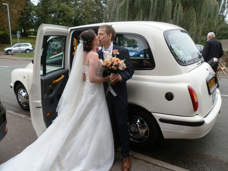 Bride and Groom kissing outside a London Taxi Wedding Car