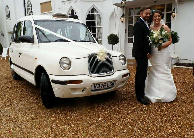 Bride and Groom beside London Taxi Wedding Car