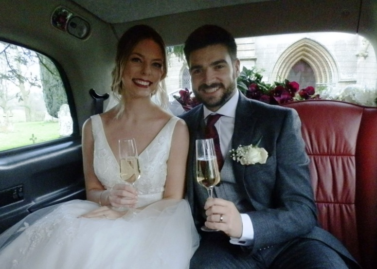 Bride and Groom drinking champagne in a London Taxi Wedding Car in Woodhall Spa