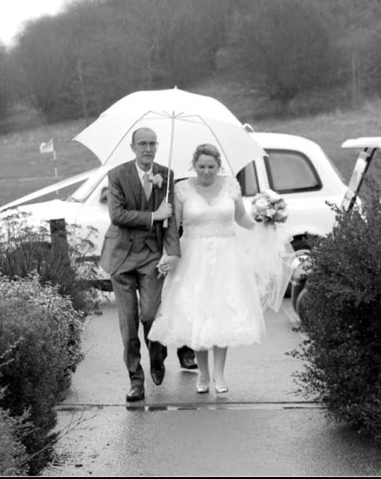 Bride and Groom under an umbrella by a London Taxi Wedding Car