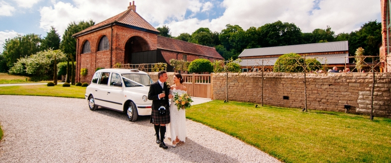 Bride and Groom by London Taxi Wedding Car at Hazel Gap Barn