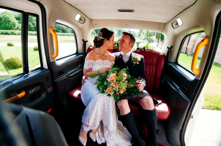 Bride and Groom in London Taxi Wedding Car at Hazel Gap barn