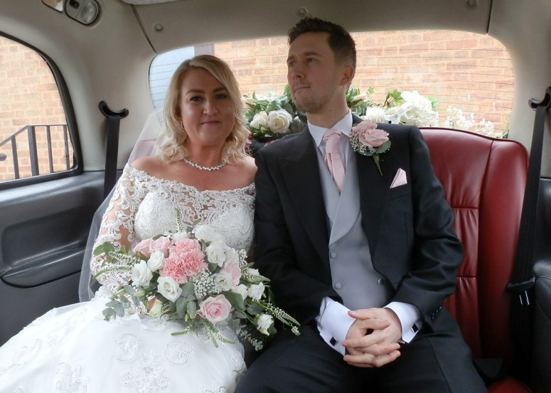 Bride and Groom in rear of London Taxi Wedding Car after their wedding