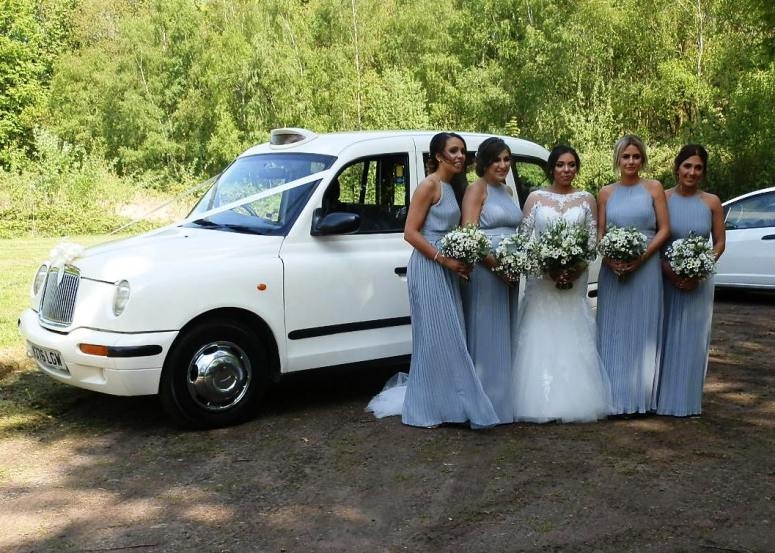 Bride and her Bridesmaids standing by London Taxi Wedding Car