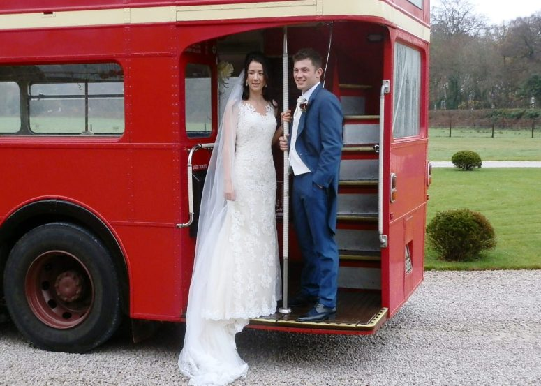 Bride and Groom on step of vintage London Bus at Hazel Gap Barn