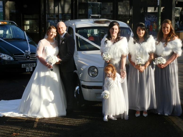 Bride, Groom and Bridesmaids standing by London Taxi Wedding Car in Winter