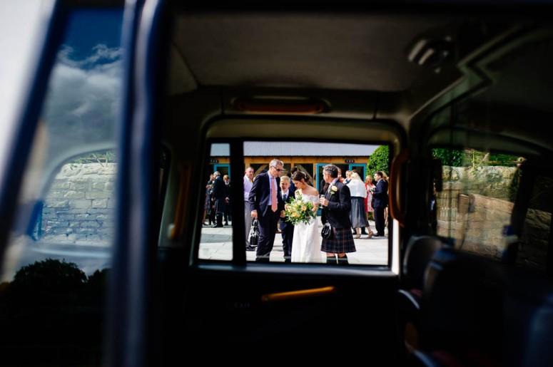 Bride and Groom by London Taxi Wedding Car at Hazel Gap Barn