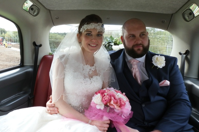 Bride and Groom in London Taxi wedding car at the Crow's Nest Barton Marina