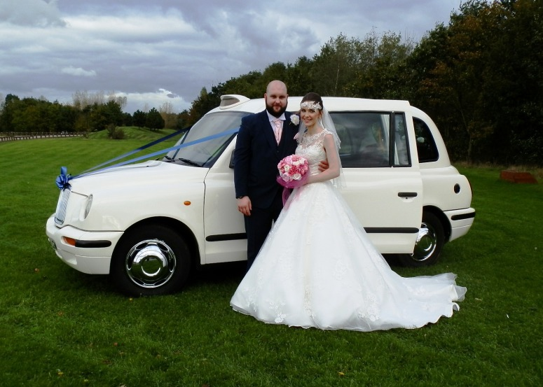 Bride & Groom standing by London Taxi wedding car at the Corw's nest Barton Marina