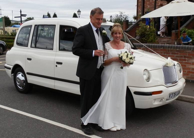 Couple standing by London Taxi wedding car at The Crow's Nest Barton Marina